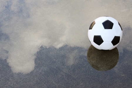 football pitch: soccer football on wet ground with water reflection cloud and sky