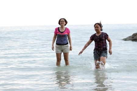 girl on woman playing in sea water  photo