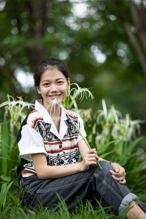 teen age sitting in the garden with white lily flower in hand Stock Photo - 16782813
