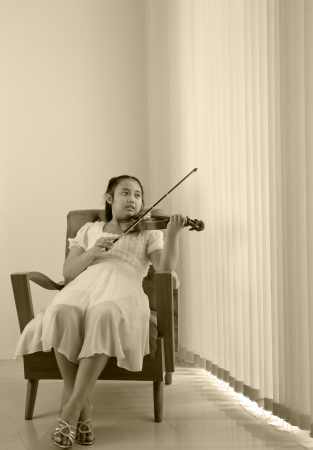 girl playing violin at home studio sepia color tone  photo