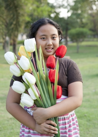 asian tulips: girl hold bouquet of tulip flowers standing in  garden