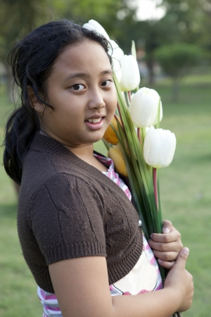 girl hold bouquet of tulip flowers standing in  garden photo