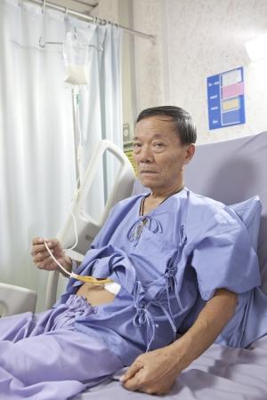 vecchio uomo paziente alimentazione cibo liquido sul letto d'ospedale