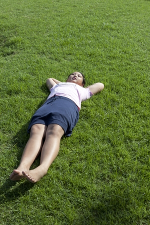 ly: girl lied on green grass field wiht morning light Stock Photo