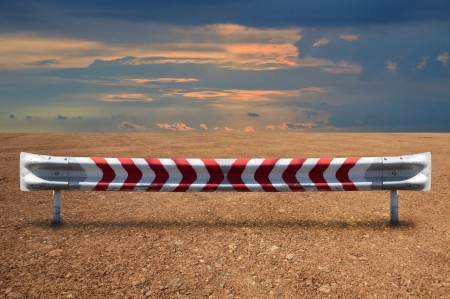 barrier: hard steel guardrail on soil land with dramatic colorful sky