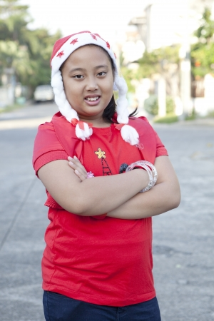 chubby girl: girl in red shirt and santa hat standing on the village street Stock Photo