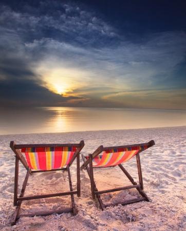 couples chairs on sand beach dusky time photo