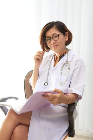 female doctor sitting in her working room with smiling face photo