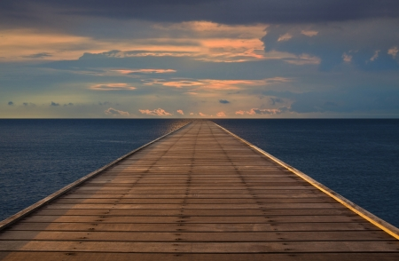 old wood bridge to the sea with cloudy sky Stock Photo - 17276284