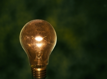 light bulb with low key green  background conception for idea creative photo