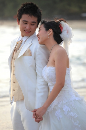beside: couple of young man and woman in wedding suit standing beside sea beach Stock Photo