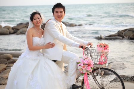 asian bride: couple of young man and woman in wedding suit ridiing old bicycle on sand beach