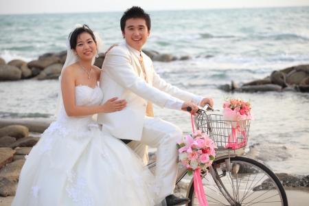 heiraten: paar junge Mann und Frau in Hochzeitsanzug ridiing altes Fahrrad auf Sand Strand