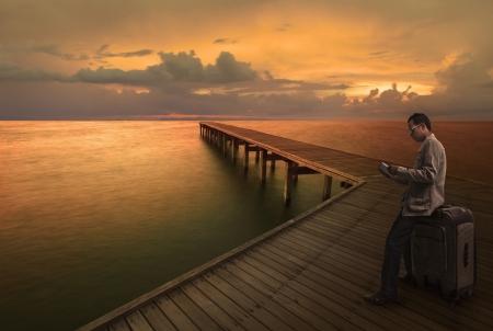 Mężczyzna czyta książkÄ™ obsÅ'ugi na mostku drewna przed podróżą do innego miejsca Zdjęcie Seryjne