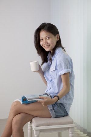 asian woman and coffee cup sitting in living room photo