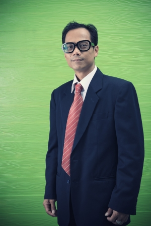 40 years old man: asian man in dark suit standing on green background