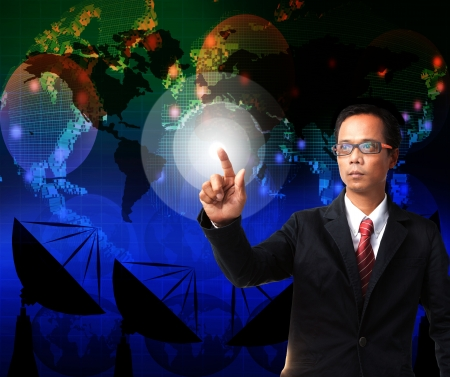telecoms: business man pointing to world map with telecommunication background use for globalization theme Stock Photo