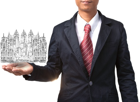 land management: business man holding drawing of modern building isolated on white