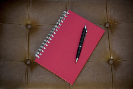 article writing: red diary on brown leather Stock Photo