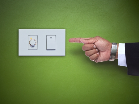 hand pointing to switch ofelectric appliance on green wall use for multipurpose photo