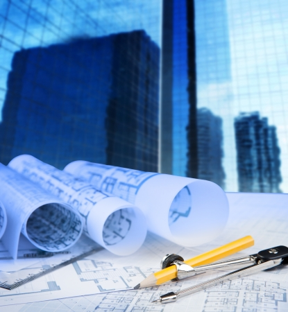 architectural drawing: compass pencil blue print and office building in background use for construction theme