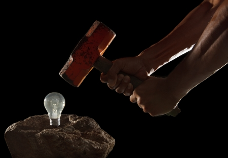 abstract of hand holding heavy hammer to breaking light bulb on the rock isolated on black photo