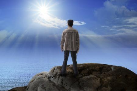 岩山の上に立って、多目的のための太陽を探している若い男