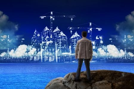 jovem de pé sobre a rocha e olhando para a construção de utilização na construção para a construção de indústrias de negócios