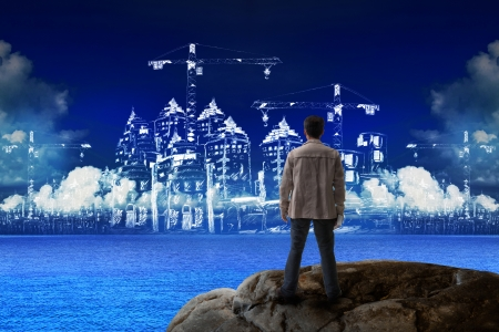 junger Mann, der auf einem Felsen und schaut auf Hochbau Verwendung für Bauindustrie Geschäft