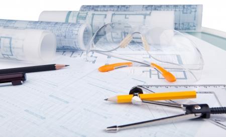 óculos de segurança e escrevendo equipamentos do arquiteto na mesa de trabalho