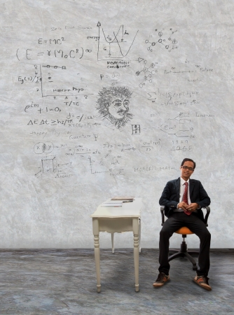 man sitting on desk and physic formula on wall use for knowledge topic and related photo