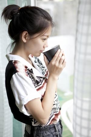 jovem mulher e uma ch�vena de caf� no uso da m�o para a bebida quente e tema relacionado
