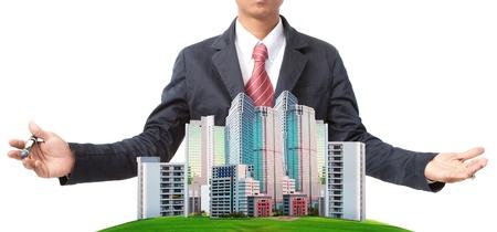 жилье: деловой человек и современное здание на зеленой травой поле использования земельных тему управления