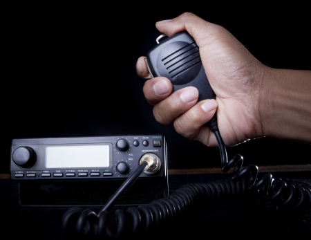 beginner: hand of Amateur radio holding speaker and press for radio communication theme