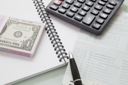stack of bank note and pen calculator on note book use for business and accounting theme photo
