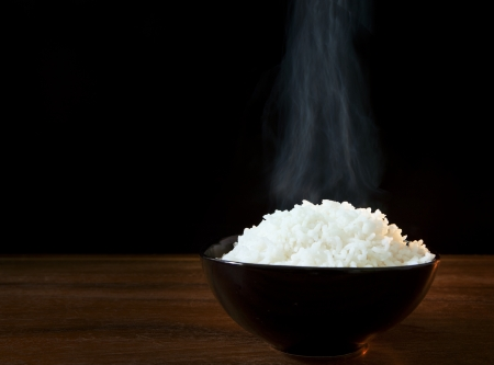 black rice: white steam rice in black ceramic bowl with smoke on black use for food topic
