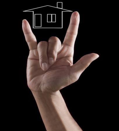 land management: hand i love you on black with home outline use for housing topic  Stock Photo