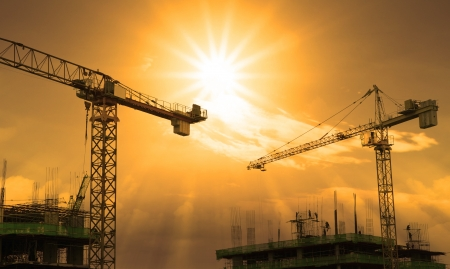 property management: crane and building construction and sun set sky Stock Photo
