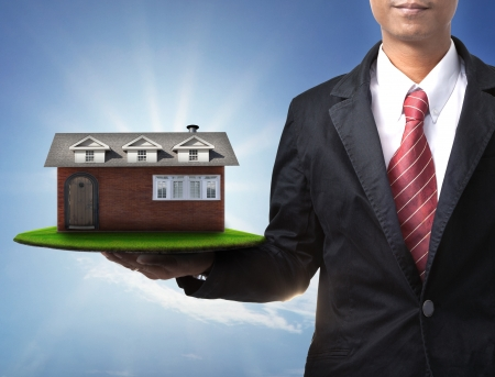 good investment: new house on business man hand Stock Photo