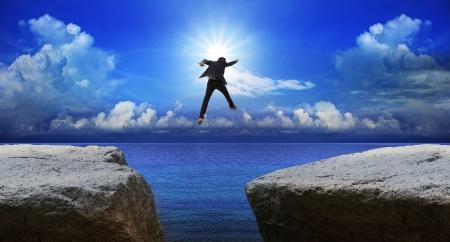 ビジネスの男性がリスク意思決定と次の崖へのジャンプ