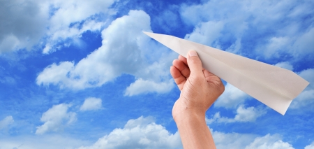 hand throwing paper plane to blue sky seem freedom