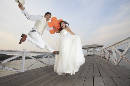 wedding beach: couple of groom and bride  in wedding suit  jumping with glad emotion on wood bridge  use for wedding and honey moon ceremony theme