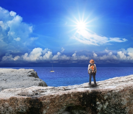 back of young man standing on rock cliff and looking to sea photo