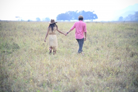 man and women holding hand and walking in grass field  photo