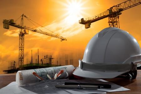planos arquitecto: archivo del casco de seguridad y pland arquitecto en la mesa de madera con escena de la puesta del sol y la construcci�n de edificios