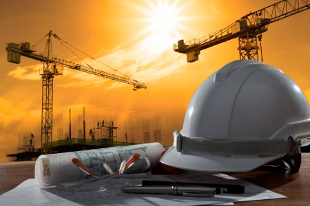 job site: file of safety helmet and architect pland on wood table with sunset scene and building construction Stock Photo