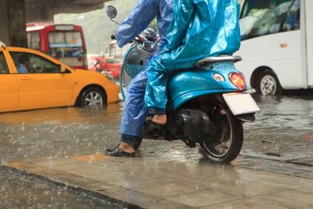 uomo sotto la pioggia: due uomo che indossa impermeabile equitazione moto Archivio Fotografico