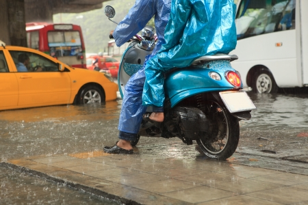 out in town: two man wearing raincoat riding motorcycle  Stock Photo