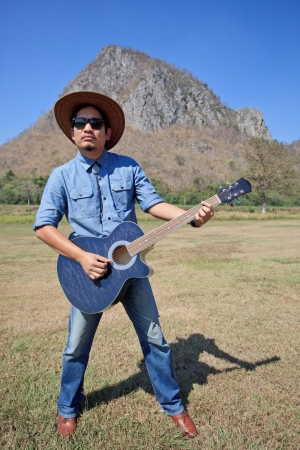 man standing and playing folk guitar with mountain behind for multipurpose photo