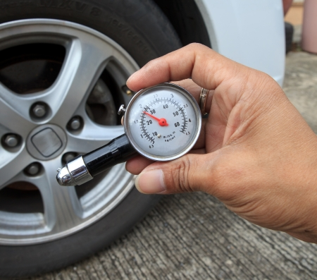 checking tire air pressure with meter  gauge before traveling for multipurpose photo